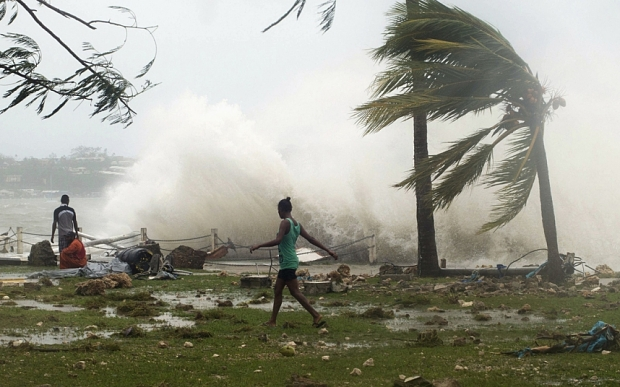 Local residents walk past debris as a wave breaks nearby in Port Vila, the capital city of the Pacific island nation of Vanuatu