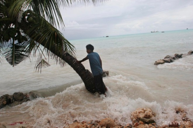 Pita Meanke, of Betio village, stands beside a tree as he watches the 'king tides' crash through the sea wall his family built onto his family property, on the South Pacific island of Kiribati.